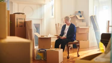 An older woman looks at a photo in her living room, surrounded by moving boxes.