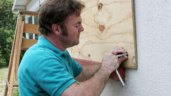 A homeowner puts plywood over his windows to protect them from winds