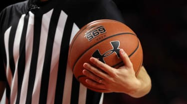A referee holds an Under Armour basketball