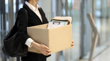 A woman who has lost her job is carrying her office possessions in a box