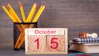 picture of wooden calendar showing October 15 and sitting on a desk