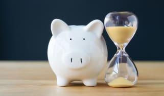 A piggy bank sits next to an hour glass.