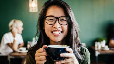 Young woman drinking coffee and smiling.