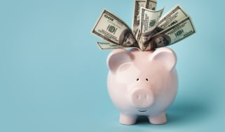 """""""A smiling pink piggybank stuffed with $100 dollar bills, on blue background with copy space.You may also like:"""""""