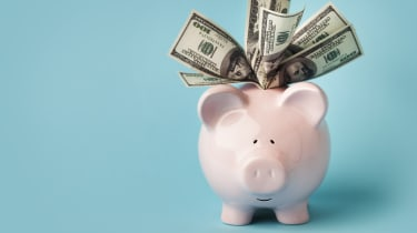 """A smiling pink piggybank stuffed with $100 dollar bills, on blue background with copy space.You may also like:"""
