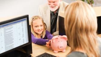 A little girl hands a piggy bank to a bank teller.