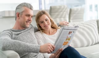 Happy loving couple at home reading a magazine and sitting on the sofa relaxing