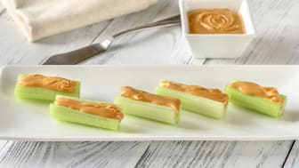 Peanut butter in a dish and on cut stalks of celery