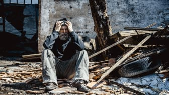 picture of distraught man sitting in front of destroyed house