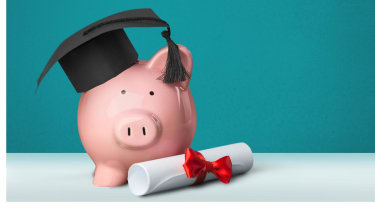 Apiggybank wearing a graduation cap sits on a table next to a rolled-up diploma