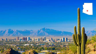 An image of the skyline of Phoenix, Ariz., with a cactus forefront and mountains behind the city