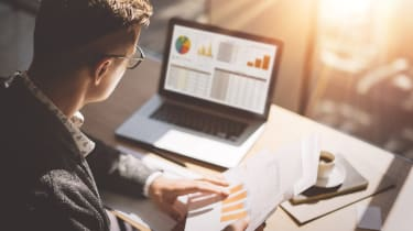 Young finance market analyst in eyeglasses working at sunny office on laptop while sitting at wooden table.Businessman analyze document in his hands.Graphs and diagramm on notebook screen.Blu