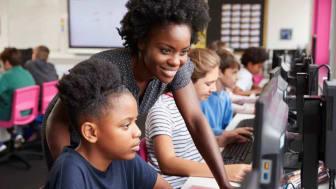 Female teacher overlooking student's work on computer