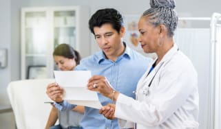 A doctor discussing a document with a patient.