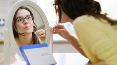 picture of woman looking in a mirror while using a home COVID-19 test kit