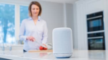 Woman Working In Kitchen With Smart Speaker In Foreground