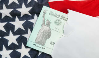 picture of envelope with government check in it sitting on an American flag