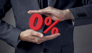 A man in a suit squeezes a 0% symbol.