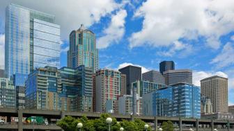 Seattle Washington city skyline along the waterfront on a blue sky cloudy day