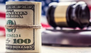 A roll of money next to a gavel