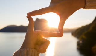 A pair of hands frame the sun between them.