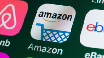 The buttons of the online shopping app Amazon, surrounded by Airbnb, ebay, News and other apps on the screen of an iPhone.