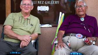 Two senior men sit on the front porch of a store in New Mexico