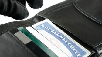 A gloved hand retrieves a social security card from a wallet