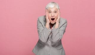 An older woman grabs her head in shock.