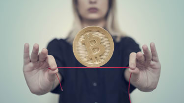 A woman balances a bitcoin on a red tightrope.