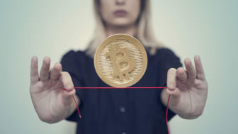 A woman balances bitcoin on a red rope.