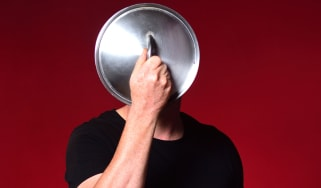 A man holds a cooking pot lid in front of his face.