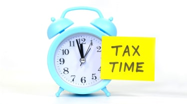 """picture of alarm clock with post-it note saying """"Tax Time"""" on it"""