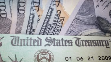 picture of a government check laying on one-hundred dollar bills