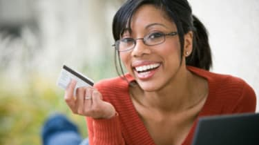Smiling African American woman shopping online with credit card and laptop