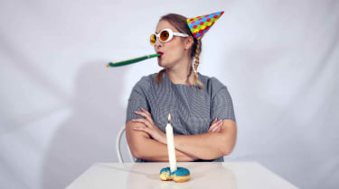 A person celebrating a birthday alone with a lone candle in a partly eaten donut.