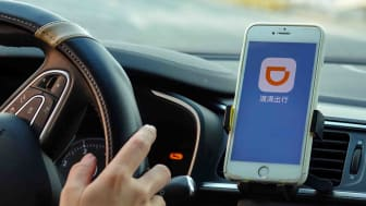 A driver has the Didi app on their phone in a cradle near their steering wheel