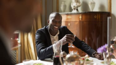 A wealthy, well-dressed man holds a glass of wine at a fine dining table.