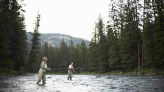 Two women fly-fishing in the Gallatin River beneath the mountains in Cameron, Montana