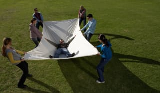 A group of people catch a person in a safety net.