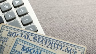 Two social security cards rest on top of a calculator which sis on a table top that provides ample room for copy and text.