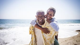 A beautiful senior black couple piggyback on the beach