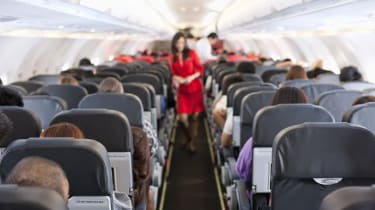 Passengers inside the cabin of a commercial airliner during flight. Shallow depth of field with focus on the seats in the foreground.