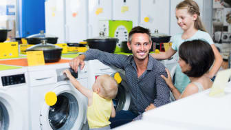 Smiling family with children choosing modern washing machine in household hypermarket