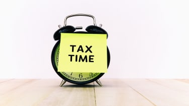 """picture of an alarm clock with a note saying """"tax time"""" on it"""