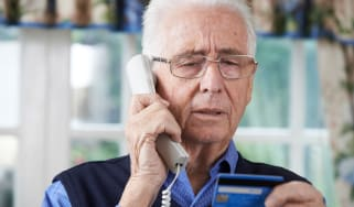 A man, who looks worried, talks on the telephone while looking at a credit card.