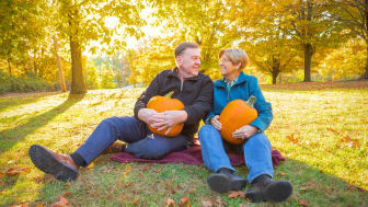 Senior couple sitting in a grassy Pennsylvania meadow holding pumpkins