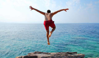 A man jumps from a rock ledge into the ocean.