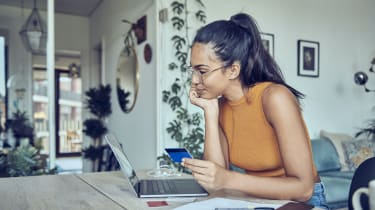 A woman is sitting at a dining table with a laptop, a credit card, and financial statements.