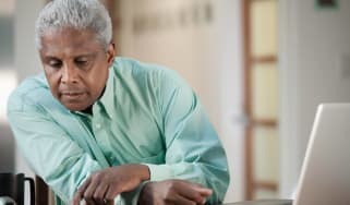 Retiree at table with open laptop looking at a calendar